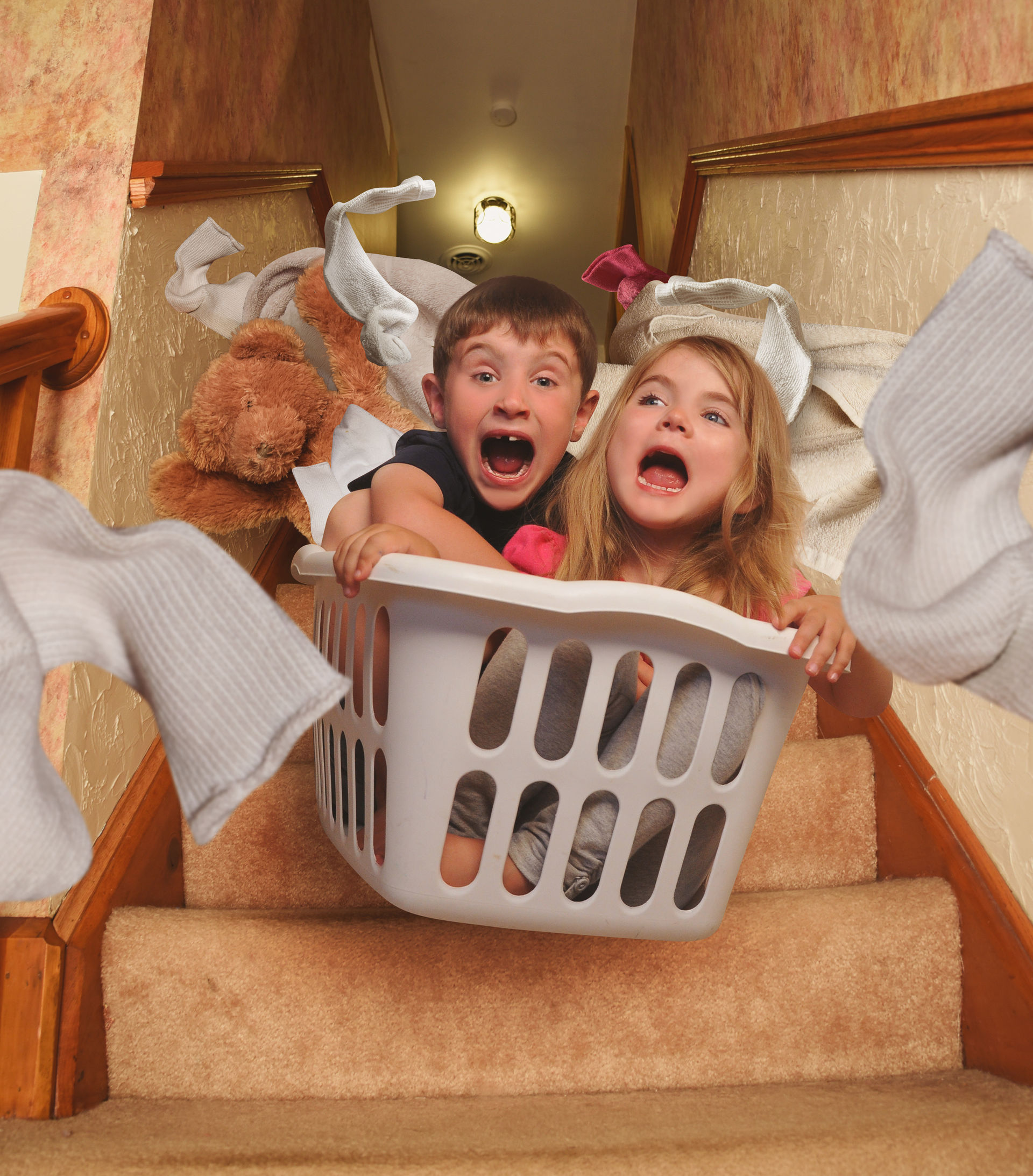 45151048 - two young children are riding in a laundrey basket down the house stairs with socks flying for a parenting, babysitter or humor concept.