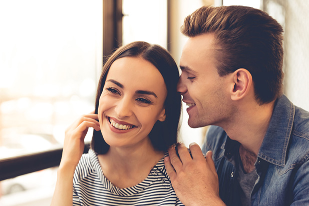65570719 - beautiful young couple is talking and smiling while resting in cafe